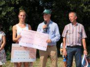 Auf dem Foto ist die Spendenübergabe bei dem Zwischenstopp der Radfahrer in Hetzerath zu sehen.